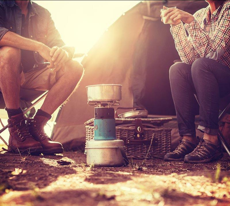 Campers sitting around a portable stove.