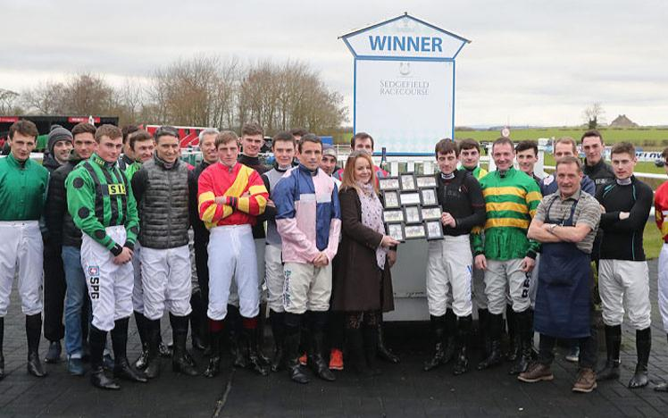 Group of jockeys posing for a photo in the parade ring at Sedgefield Racecourse.
