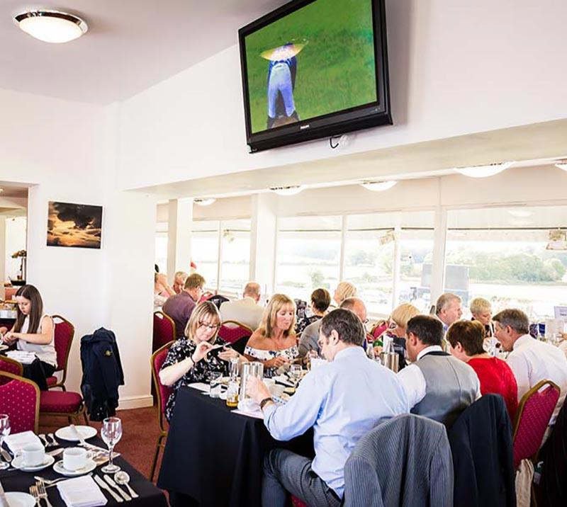 Diners enjoying their food beneath a flat screen TV showing the racing action.