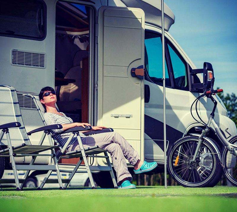 A guest relaxes outside their motor home at Sedgefield Racecourse.